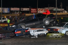 A row of cars softens the landing for the old Cadillac on Monday, July 4, 2011, during the Boone Speedway eve of destruction.
