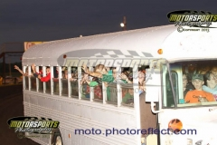 Kids wave from the bus as they enjoy a free ride around the track on the Boone Speedway bus.